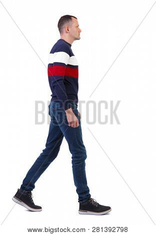 Side view of going  handsome man in pullover. walking young guy . Rear view people collection.  backside view of person.  Isolated over white. Stylish man walks by carefully looking in front of him.