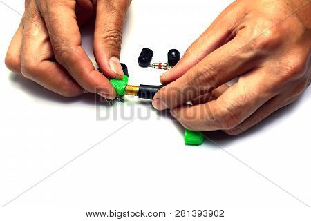 The Tyre Pressure Valve And The Green Cover  In Hand On White Isolated Background
