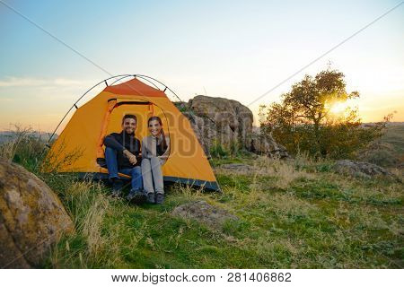 Young Couple Sitting near Tent at Beautirul Evening in the Mountains. Adventure and Family Travel Concept.