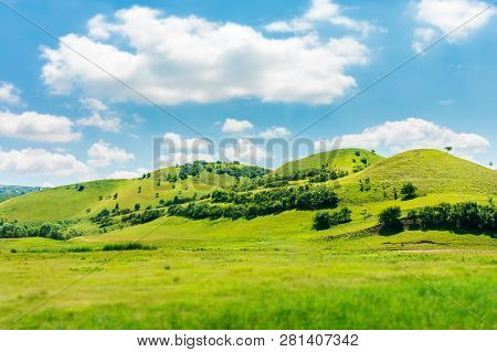 Green Hill In Summer Landscape. Beautiful Countryside Scenery. Fluffy Clouds On A Bright Blue Sky. T