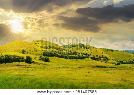 Green Hill In Summer Landscape At Sunset In Evening Light. Beautiful Countryside Scenery.  Tilt-shif