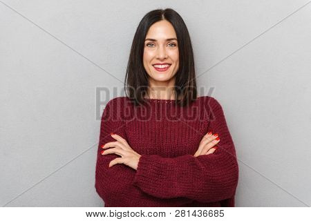 Image of beautiful young woman dressed in burgundy sweater posing isolated over grey wall background.