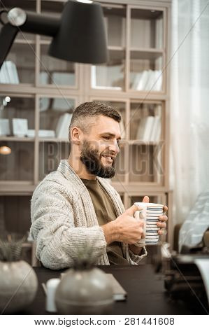 Smiling Bearded Man Drinking Hot Tea While Sitting At The Desk