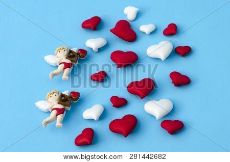 Two Little Cupids And A Few Little Red And White Hearts Against Blue Background