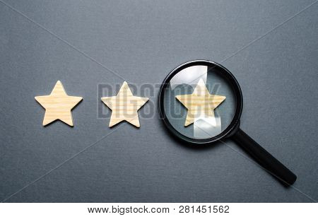 Three Stars And A Magnifying Glass On A Gray Background. Authentication Of The Third Star, Rating Fr