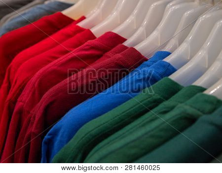 Colorful Shirt On Hang For Sale In Shop. Bright Color T-shirt On Plastic Hanger. Summer Seasonal Wea