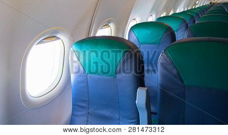 Empty Airplane Chairs And Sunlight In Illuminator. Aircraft Interior Photo. Empty Plane Waiting For