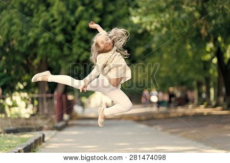 Happy Girl Jump High In Summer Park. Small Child Smile With Flying Hair In Motion Feeling Free. Fash