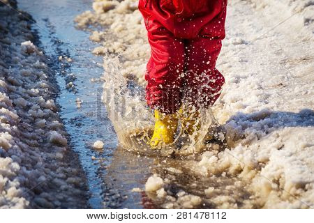 Kid Legs In Yellow Rainboots Jumping In The Ice Puddle With Melting Snow At Sunny Spring Day, Outdoo