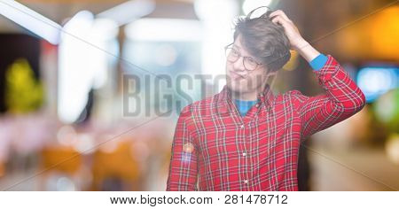Young handsome man wearing glasses over isolated background confuse and wonder about question. Uncertain with doubt, thinking with hand on head. Pensive concept.