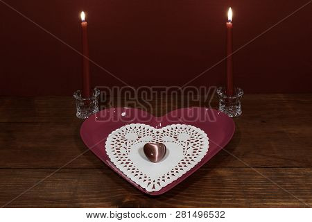 Pink Heart Shapped Plate With Dollie And Gemstone, Two Red Candles In Crystal Holoders On Wooden Tab