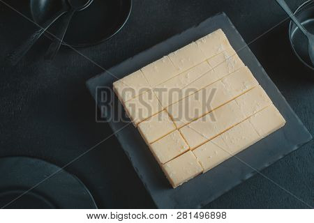 White soft chocolates on a black background with copy space. Milk Japanese gourmet chocolate close-up poster