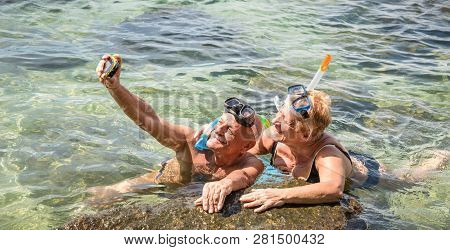 Happy Retired Couple Taking Selfie In Tropical Sea Excursion With Water Camera And Snorkel Mask - Bo