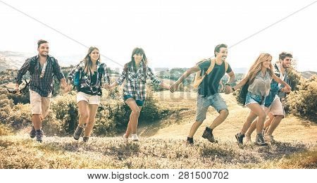 Group of friends running on grass meadow on country side - Happy friendship and freedom concept with young millenial people moving free at camping experience - Vintage desaturated filter poster