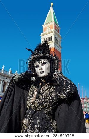 VENICE, ITALY - FEBRUARY 18, 2017: Woman wearing vintage black costume, gloves, hat and white mask  posing on San Marco Square during traditional Carnival taking place each year in Venice, Italy.