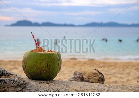 Green Coconut Drink With Straw On Sea Beach Sand. Coconut Juice On Tropical Seashore. White Sand Bea