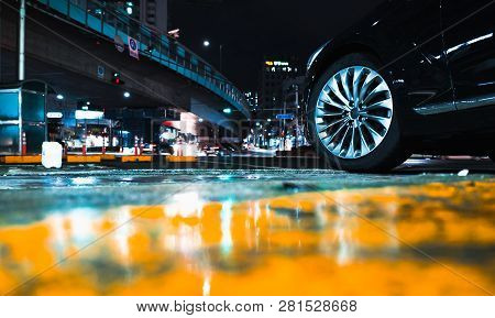 Abstract Night City Background With Car Wheel On Wet Urban Road