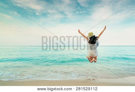 Happy Young Woman In Casual Style Fashion And Straw Hat Jumping At Sand Beach. Relaxing, Fun, And En