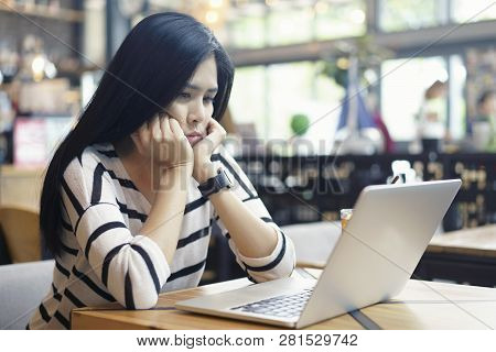 Serious Asian Woman Thinking Of Problem To Working A Difficult Assignment In A Desktop, Using Laptop