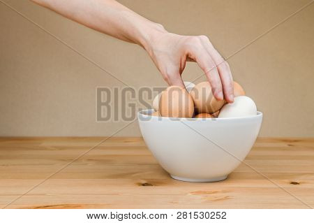 Female Hand Taking One Egg From White Bowl On A Table .