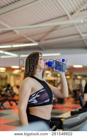 Gym Woman Working Out Drinking Water Smiling Happy Standing By Moonwalker Fitness Machines. Beautifu