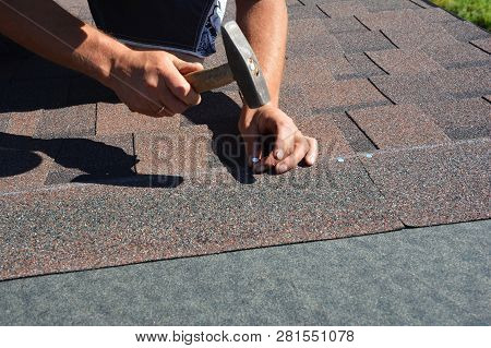 Roofing Construction. Roofer Installing Asphalt Shingles On House Construction Roof Corner With Hamm
