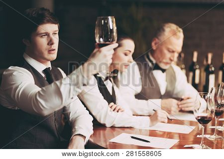 Young Experienced Sommelier Looks At Sediment Of Wine In Glass. Wine Tasting. Confident Sommelier Ch