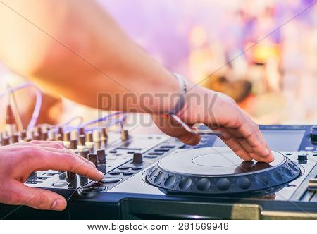 Dj Mixing At Beach Party Festival With People Dancing In The Background - Deejay Playing Music Mixer