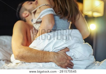 Passionate young couple having sex on the bed at home - Intimate and sensual moments of a couple making love in the bedroom - Adultery, intercourse, love, sexual concept - Focus on the male hand poster