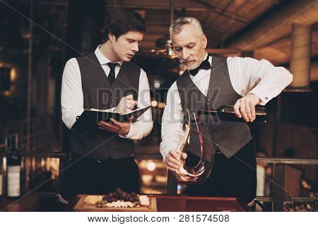 Two Experienced Sommeliers Taste Wine. Sommelier Pours Red Wine From Bottle Into Decanter. Wine Tast