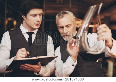 Two Men Sommelier Tasting Wine In Restaurant Looking At Decanter With Wine. Tasting Of Elite Drinks.