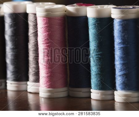 Flat detail of threads of colors pink, light blue, blue, green, gray poster