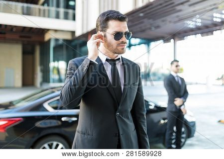 Handsome Bodyguard Listening To Earpiece With Car Parked On Street In City
