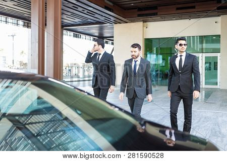 Wealthy Businessman With Smart Looking Bodyguards Walking Towards Car