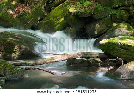 Small Stream Among The Rocks. Beautiful Nature Scenery In Spring. Moss On Boulders. Trunk Above The