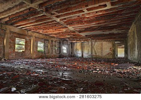 Interior Of An Abandoned Building With Rubble And Debris - Desolate Hall Of An Old Factory In Ruins