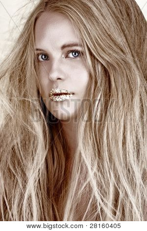 Close-up fashion portrait of a sensual beautiful blond woman model face with gold leaf on her lips and tangled messy long hair.