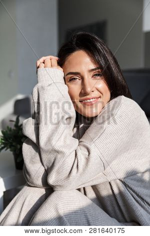 Photo of middle-aged sunlit woman 30s smiling while sitting on couch in bright apartment in the sunshine poster