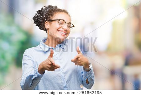 Young braided hair african american business girl wearing glasses over isolated background pointing fingers to camera with happy and funny face. Good energy and vibes.