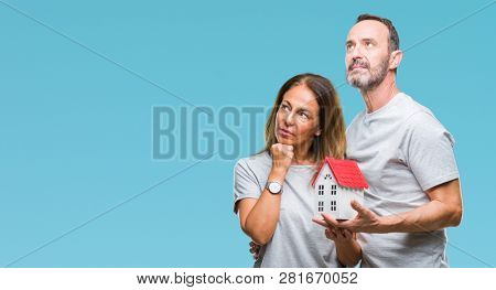 Middle age hispanic casual couple buying new house over isolated background serious face thinking about question, very confused idea