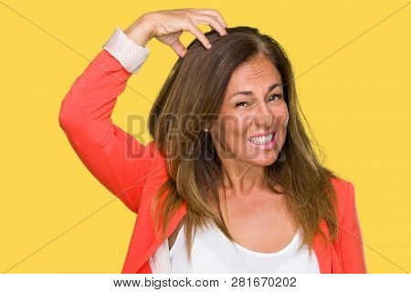 Beautiful middle age business adult woman over isolated background confuse and wonder about question. Uncertain with doubt, thinking with hand on head. Pensive concept.