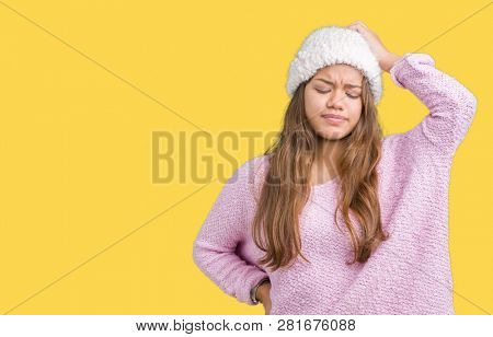 Young beautiful brunette woman wearing sweater and winter hat over isolated background confuse and wonder about question. Uncertain with doubt, thinking with hand on head. Pensive concept.