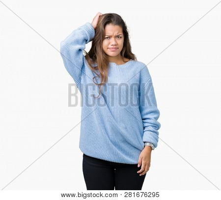 Young beautiful brunette woman wearing blue winter sweater over isolated background confuse and wonder about question. Uncertain with doubt, thinking with hand on head. Pensive concept.