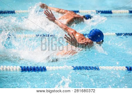 Men swimming butterfly stroke in a race, focus on water droplets, swimmers have motion blur