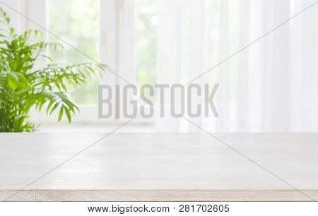 Wooden Table Top On Blurred Background Of Half Curtained Window