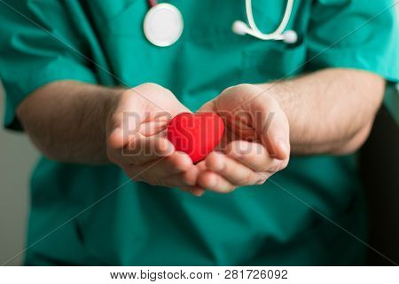 Male Doctor In Green Costume With Stethoscope Holds In Hands Bright Red Heart In The Center Of The S