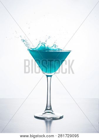 Blue Cocktail In Martini Glass With Ice Cube Splashing Into Liquid Against White Background. Blue Cu