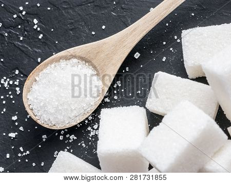 Background Of Sugar Cubes And Sugar In Spoon. White Sugar On Black Background. Sugar Cubes And Granu