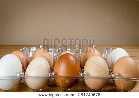 Side View Of Ten Chicken Eggs In A Plastic Box On A Table With Copy Space.