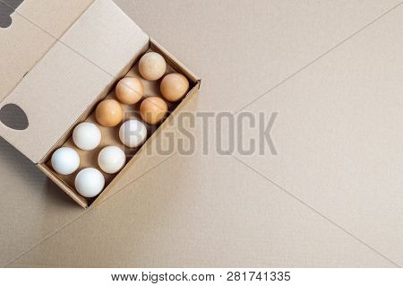 Top View Of Carton Egg Container With Fifteen Eggs On A Brown Background.